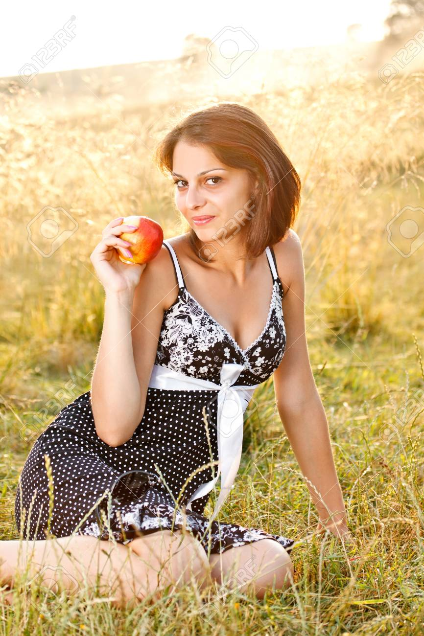 Young woman relaxing on meadow, holding fresh apple Stock Photo - 14746155