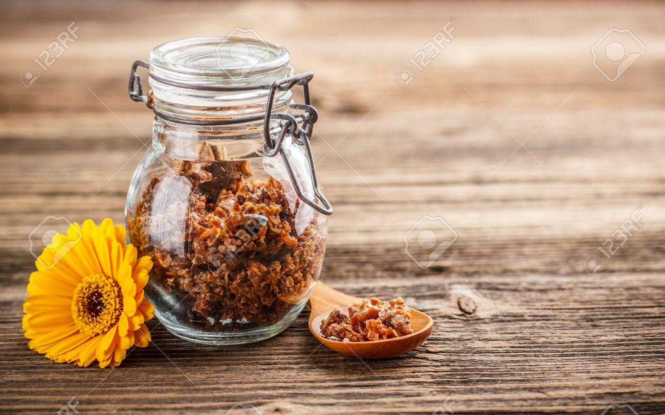 Propolis Granule In Glass Jar On Rustic Wooden Background Stock Photo