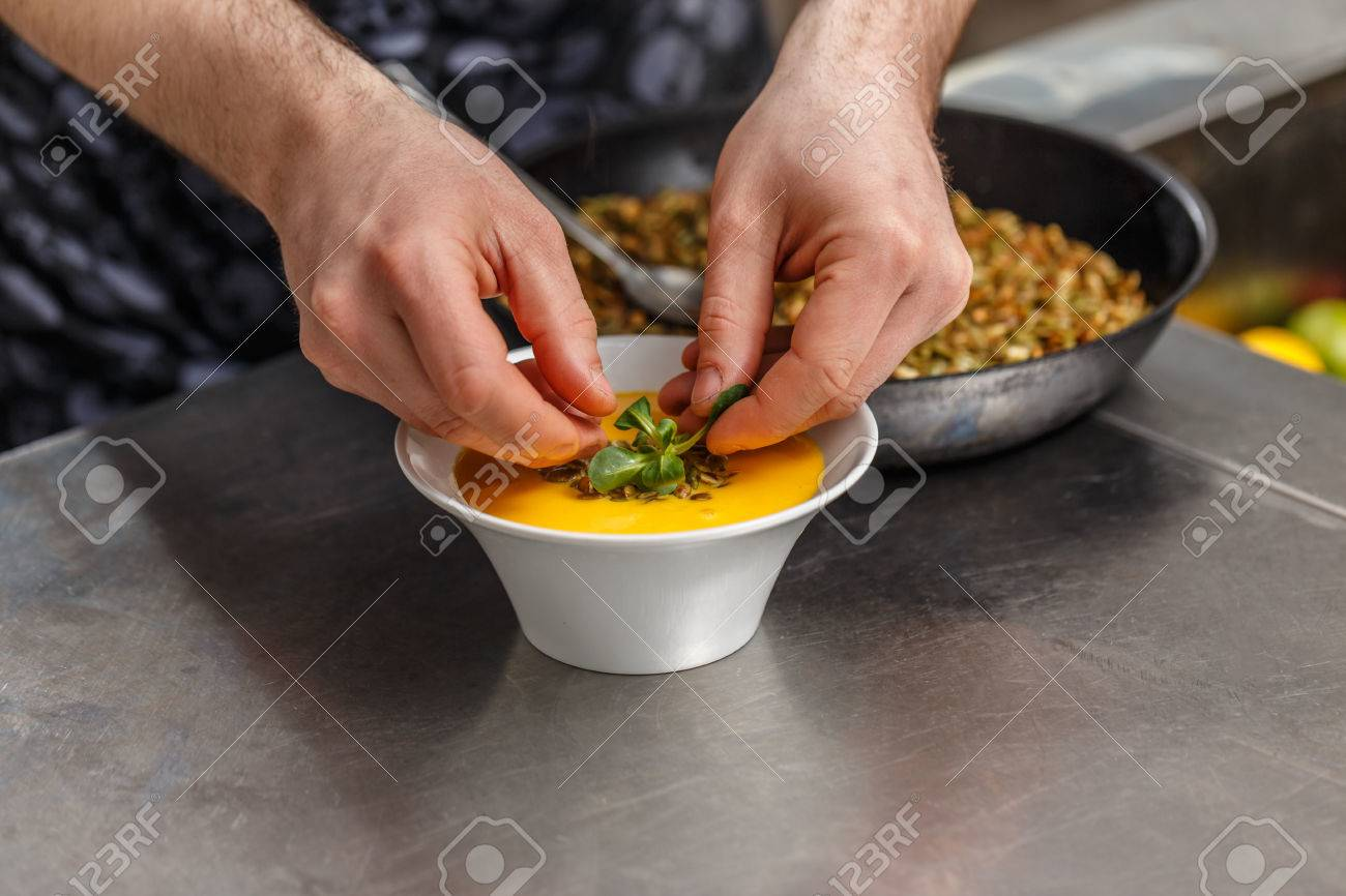 Chefs buying fresh herbs - Chef Is Decorating Ginger Carrot Soup With Fresh Herb Stock Photo 74710376