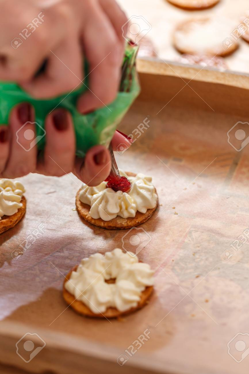 pastry chef is decorating a cake with whipped cream and jam stock