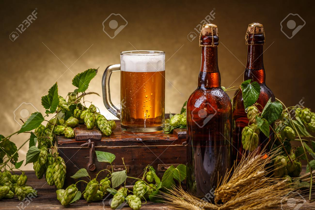 Glass And Bottles Of Beer With Green Hops Decoration On Wooden