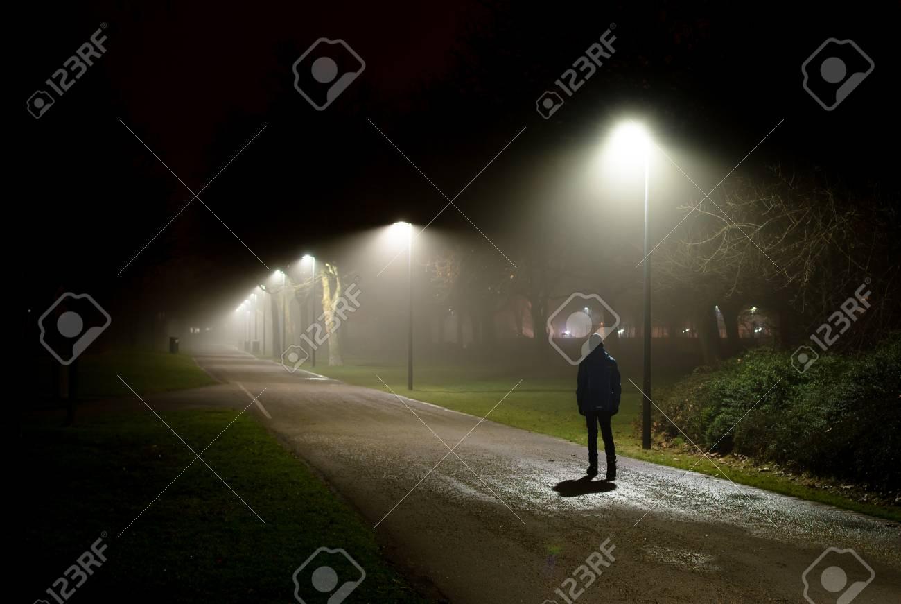 Single Person Walking on Street in the Dark Night - 99895054