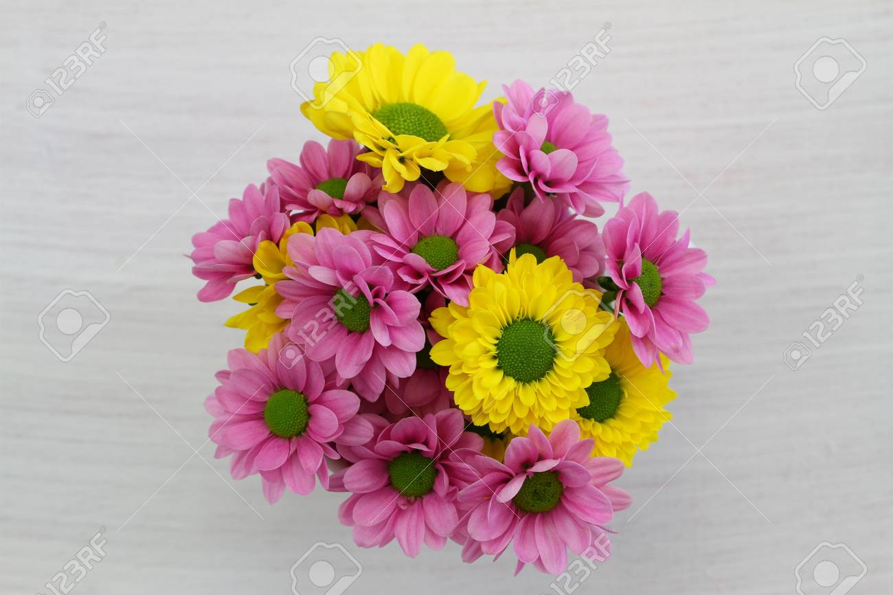 Yellow And Pink Santini Flower Bouquet On White Wood Stock Photo