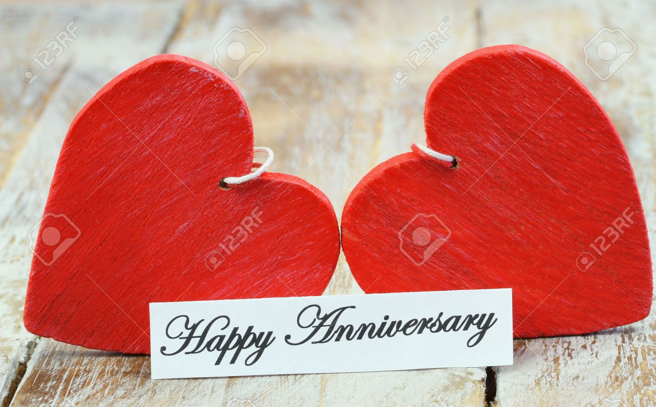 happy anniversary card with two red wooden hearts stock photo