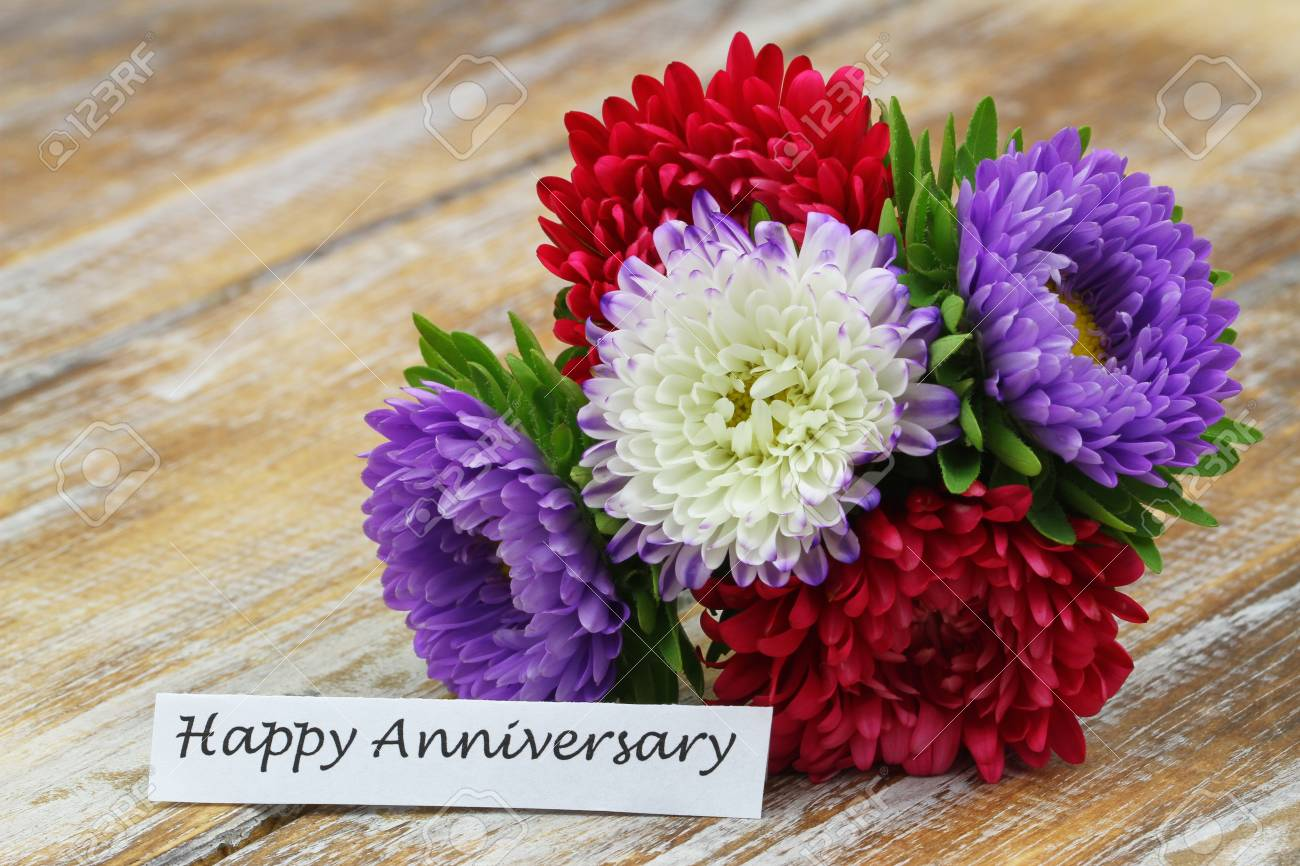 Happy anniversary card with colorful bouquet of aster flowers happy anniversary card with colorful bouquet of aster flowers on rustic wooden surface stock photo izmirmasajfo
