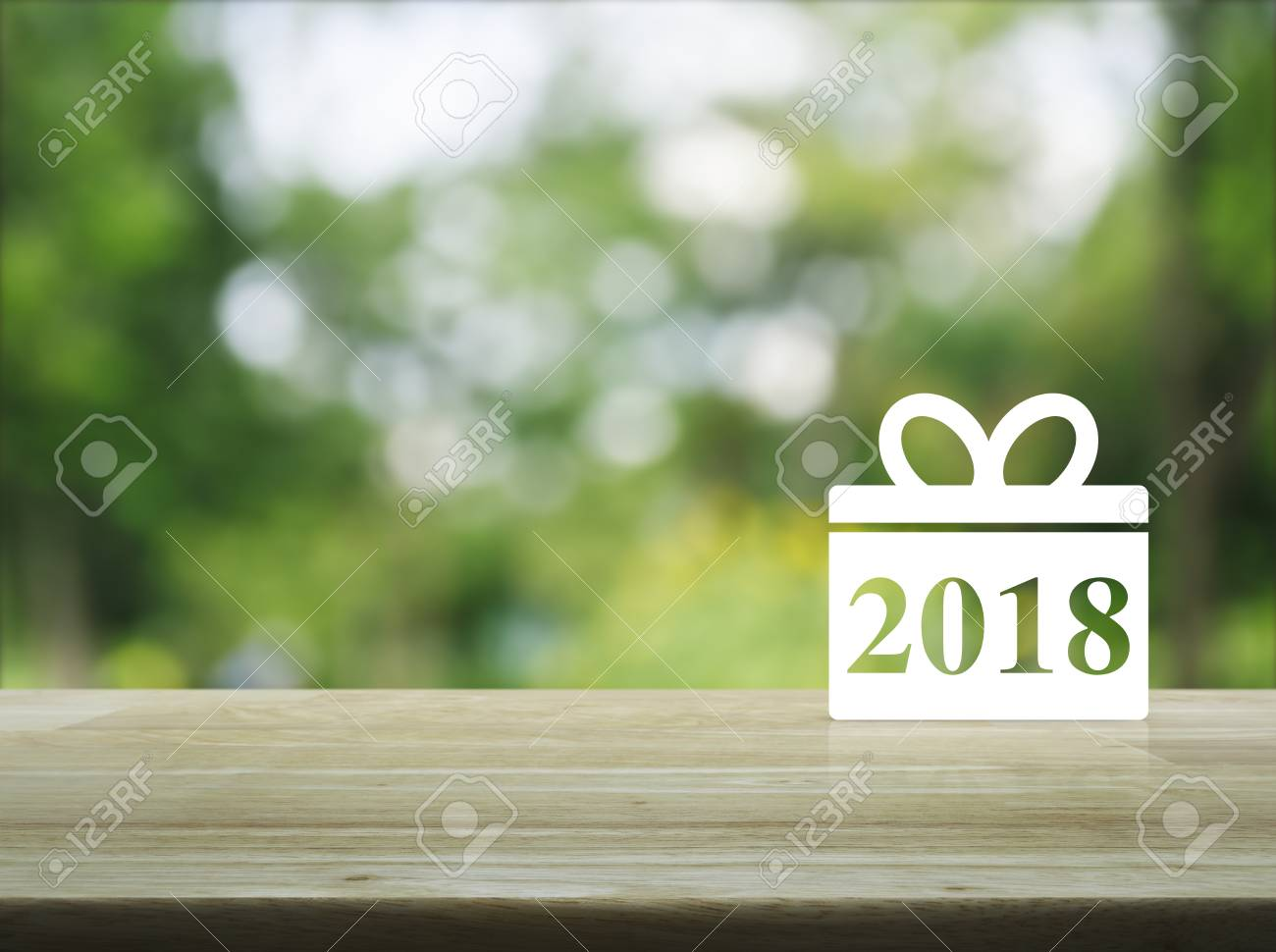 gift box happy new year 2018 icon on wooden table over blur green tree in park