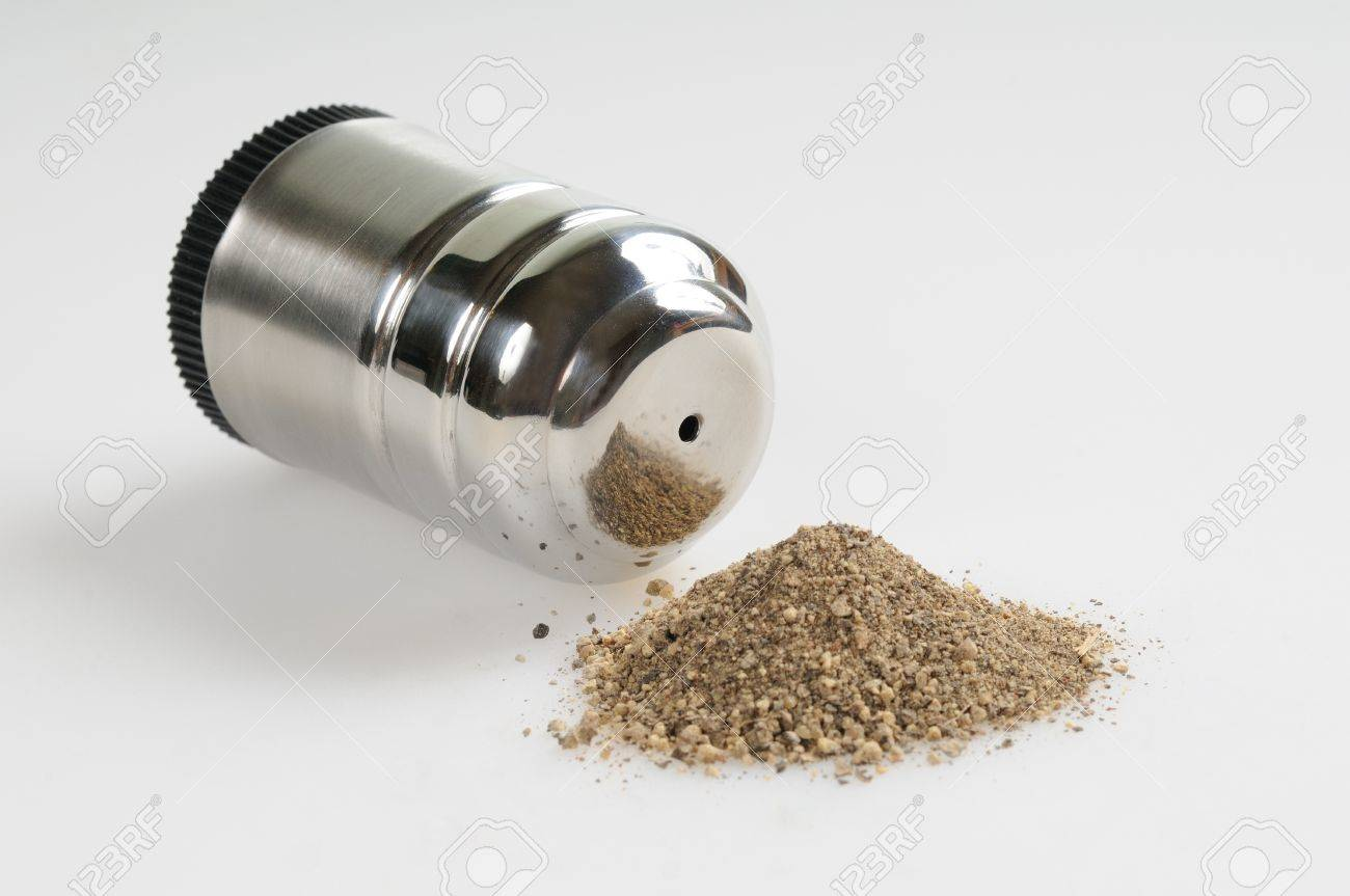 pepper shaker grey background and spilled pepper stock photo  - pepper shaker grey background and spilled pepper stock photo