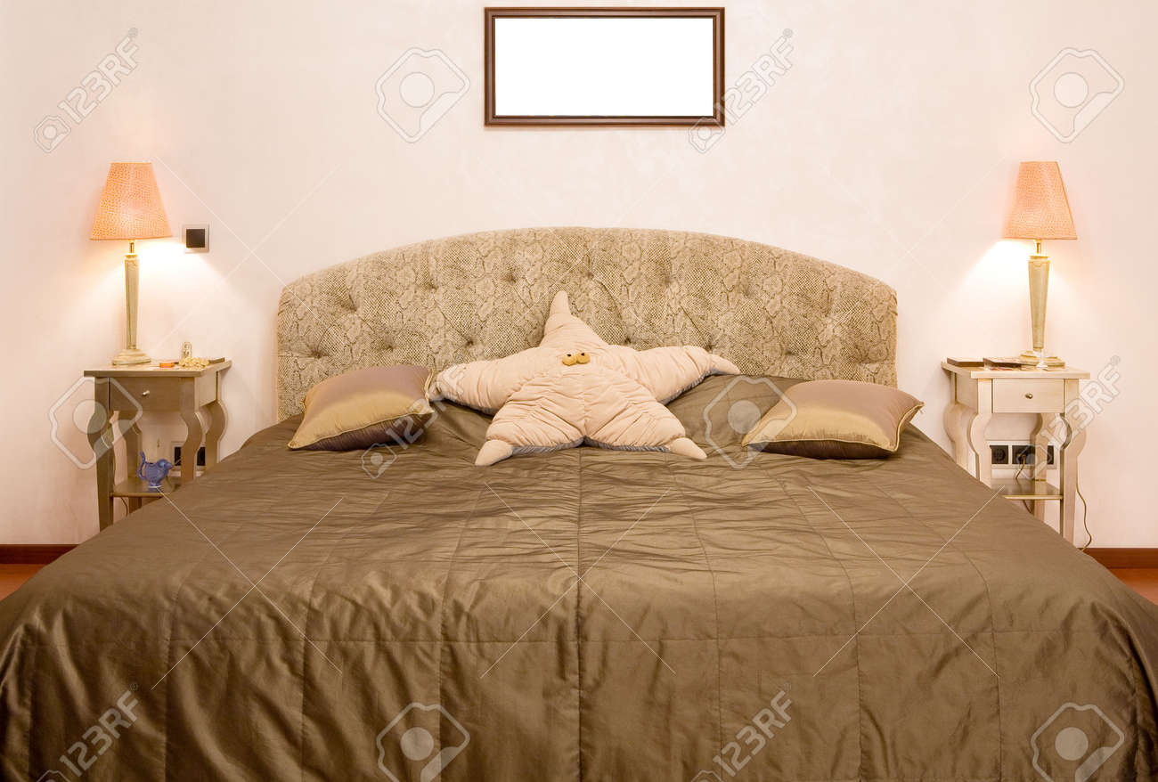 Bedroom in which there is a big bed with a coverlet of olive colour, two little tables with lamps and a pillow in the form of a star Stock Photo - 2923866