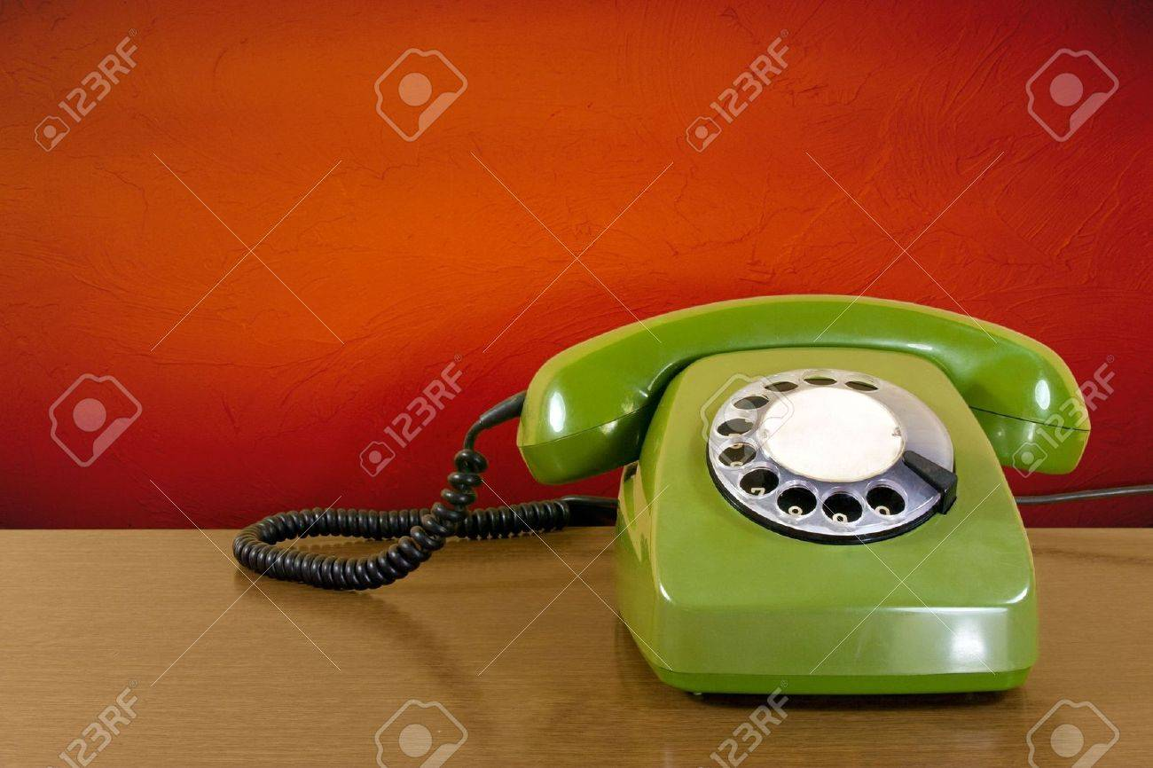 old green scratched phone against red wall background Stock Photo - 7698937