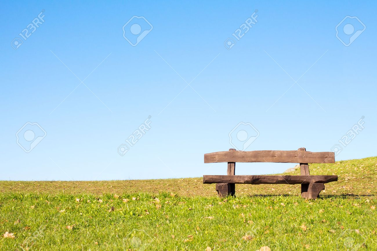 A calm place to rest and relax. An empty wooden bench over a serene blue sky waiting for a hiker or casual walker to sit and rest. - 47210341