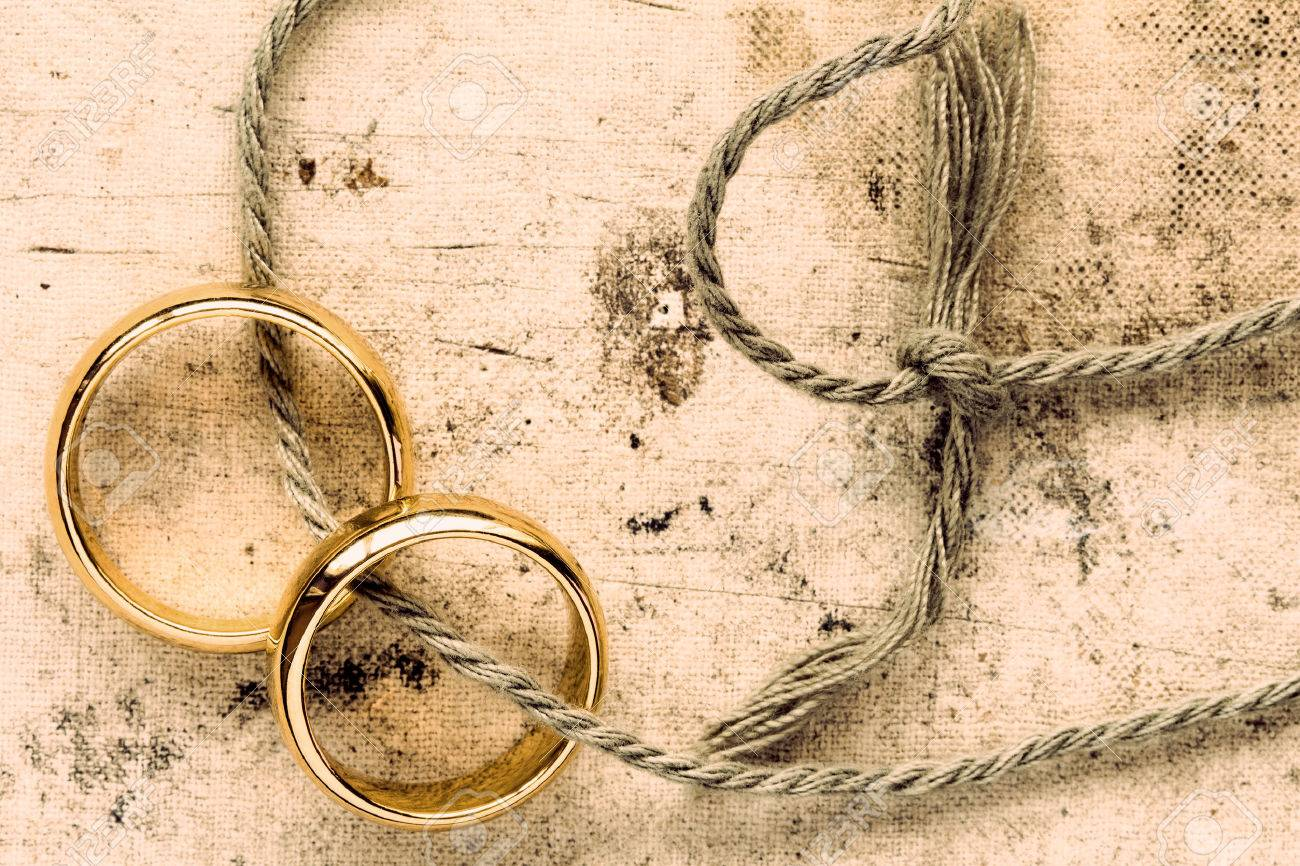 Two gold wedding rings tied with string - 58031507