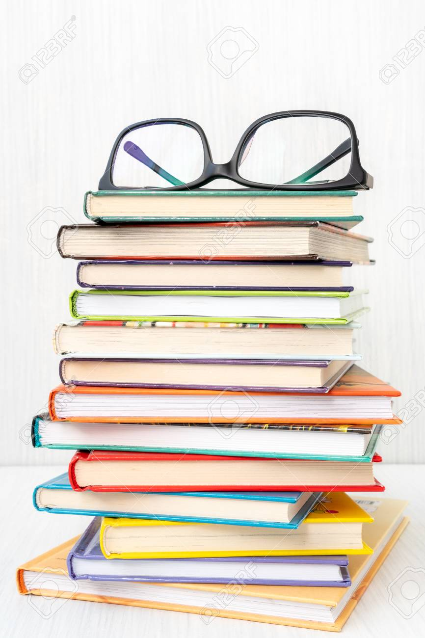 stack of books with a eyeglasses on top reading literature