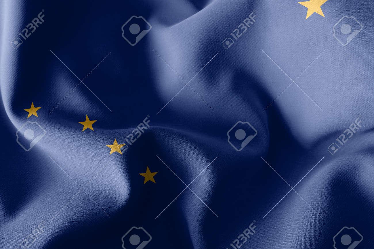 3D illustration flag of Alaska is a region of United States. Waving on the wind flag textile background - 168929071