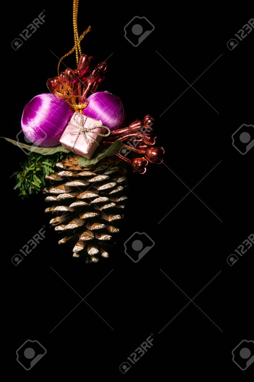 a colorfull christmas tree conifer cone decoration ornament on a black background with purple pink