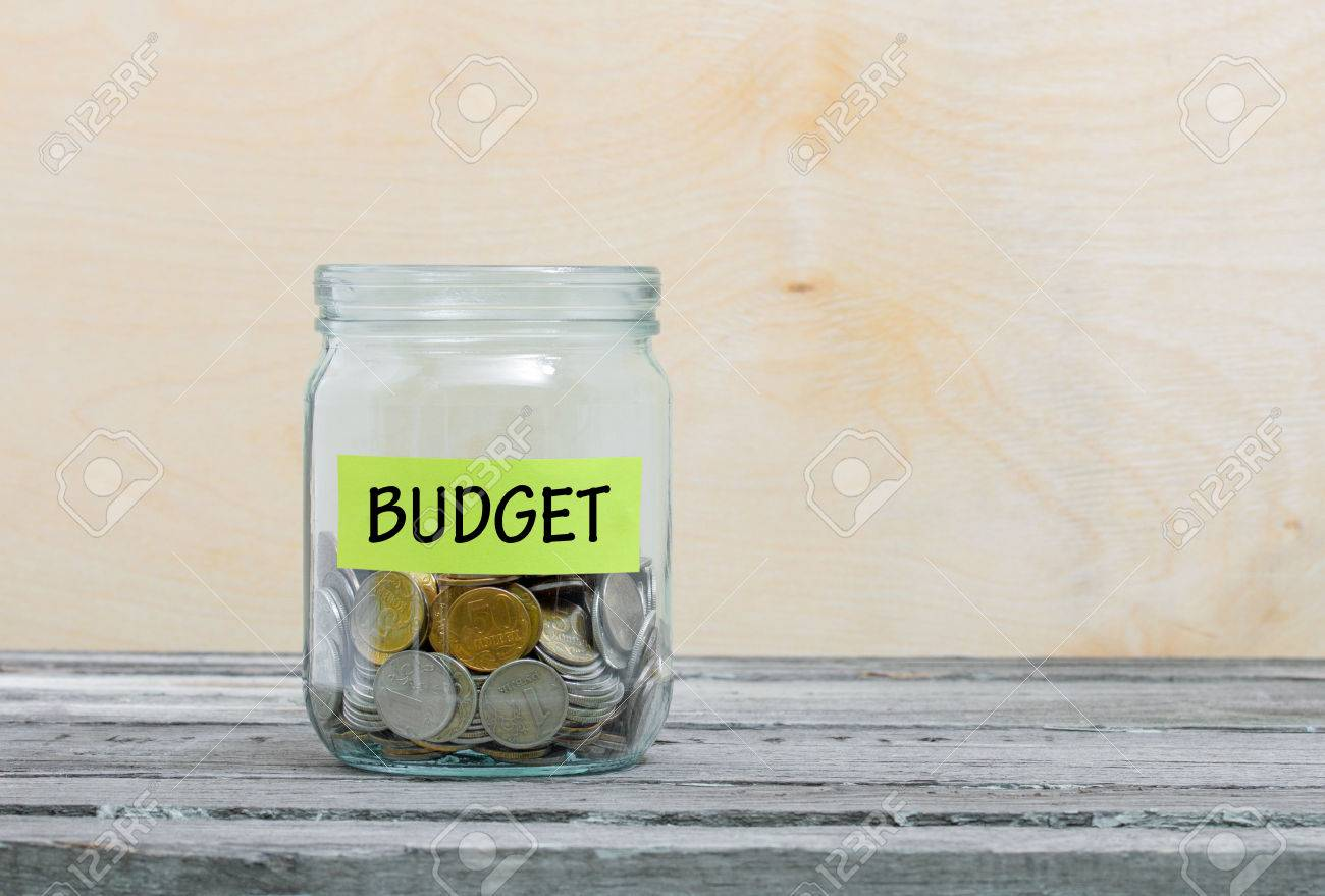 Label on a glass jar with the inscription - budget. Glass jar with coins. Financial concept on wooden background - 55369542