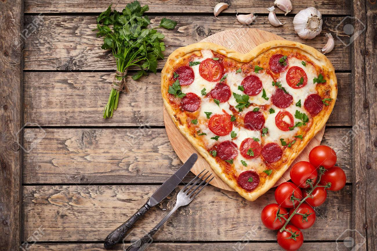 Valentines day heart shaped pizza with pepperoni, cherry tomatoes, mozzarella and parsley on vintage wooden table background. Symbol of love. Rustic style, Top view. - 51513866