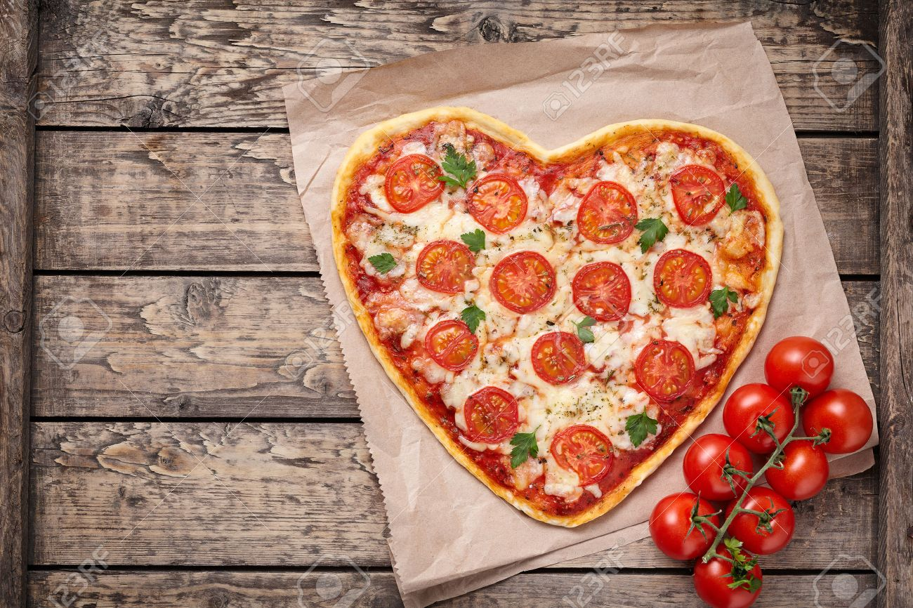 Heart shaped pizza margherita with tomatoes and mozzarella vegetarian meal on vintage wooden table background. Food concept of romantic love for Valentines Day. Rustic style and natural light. - 51514164