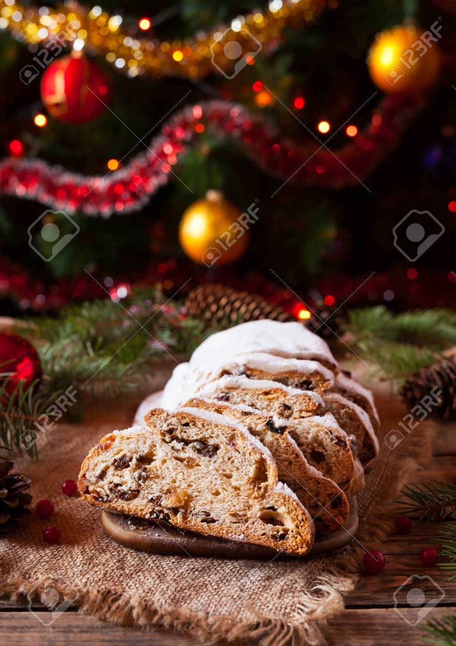 stock photo traditional german christmas cake stollen with marzipan berries nuts cinnamon raising on a rustic wooden festive table