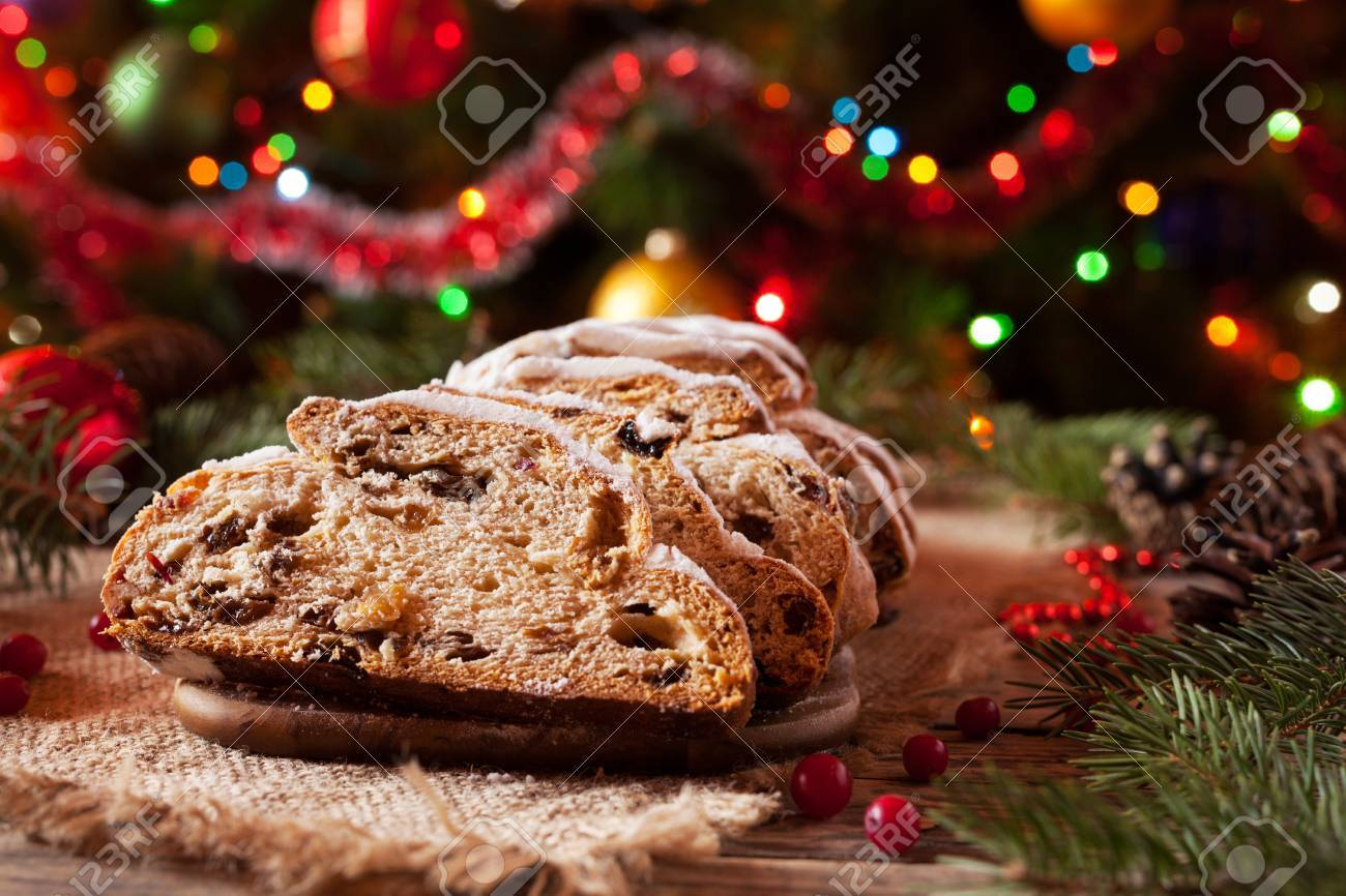 stock photo traditional dresdner german christmas cake stollen with marzipan berries nuts cinnamon raising on a rustic wooden festive table