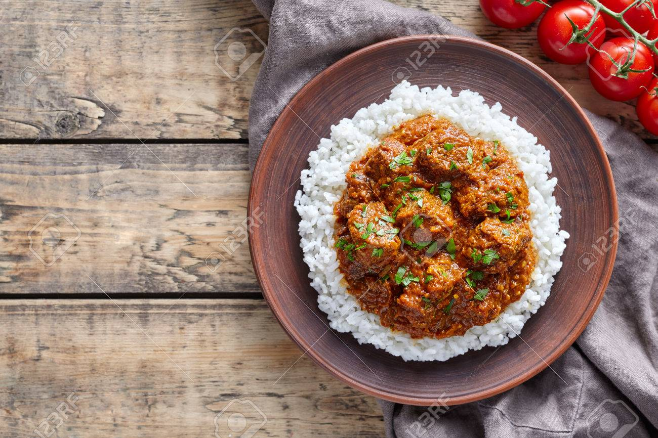 Traditional madras butter beef spicy garam masala slow cook lamb stock photo traditional madras butter beef spicy garam masala slow cook lamb food with rice and tomatoes in clay dish on vintage wooden table background forumfinder Images