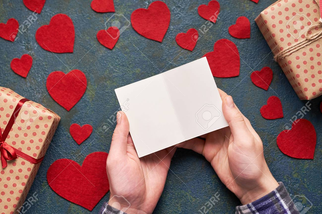 male hands holding a valentine card background with hearts and
