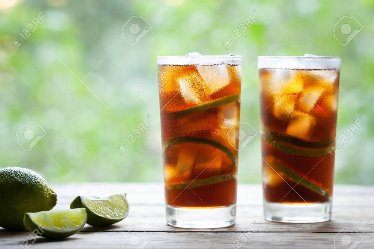Dos Copas De Cóctel Cuba Libre Con Lima Hielo Y Menta En Mesa De Madera Con Vista A La Terraza Cerrar La Bebida De Verano Copia Espacio Para Texto