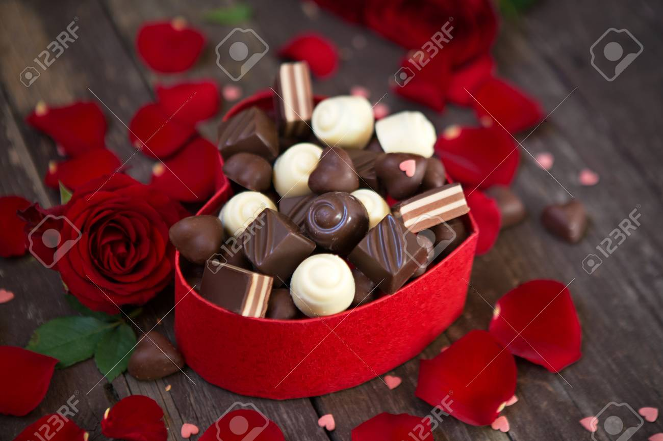 Gift box with red roses and sweet chocolates on wooden background - 72531654