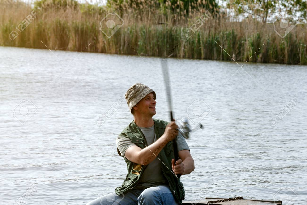 River Fishing Portrait Of Man Catching Fish In Boat Stock Photo
