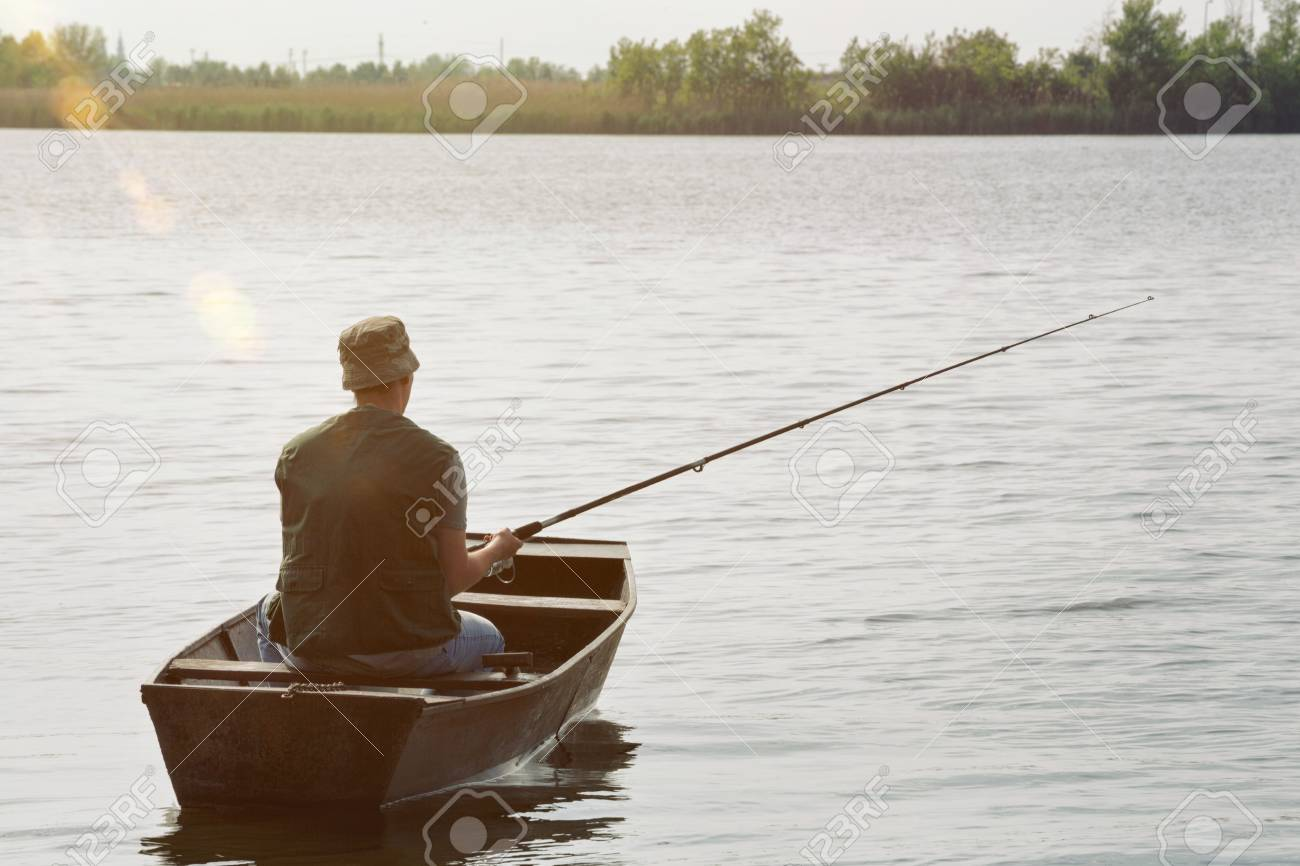 Fisherman Fishing Man Catching Fish In Boat Stock Photo Picture And