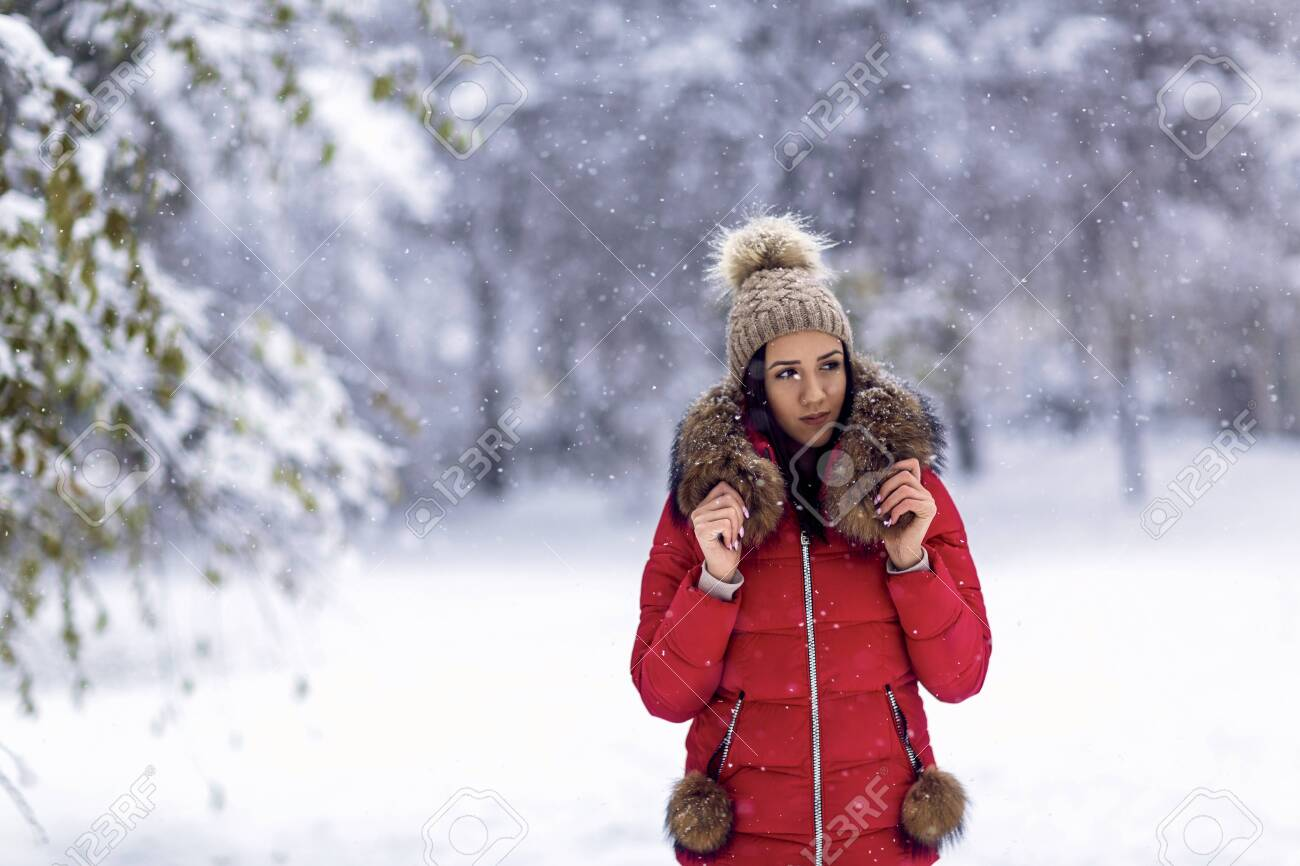 young woman enjoying in the snow.Happy girl standing outdoors in snow during winter. - 133124268