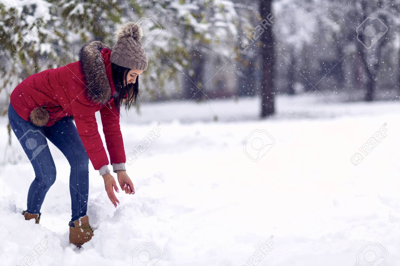 Girl playing with snow. Beautiful young woman in winter. Wintertime. Happy woman holds snowball in hands. - 133124273