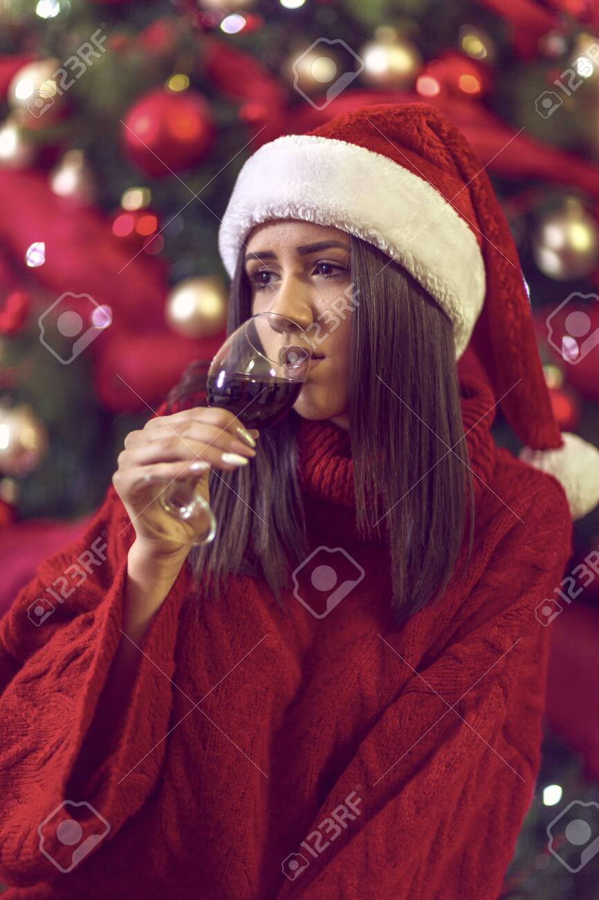 holidays, winter and people concept - young smiling woman in Santa hat by Christmas tree at home. - 133124275