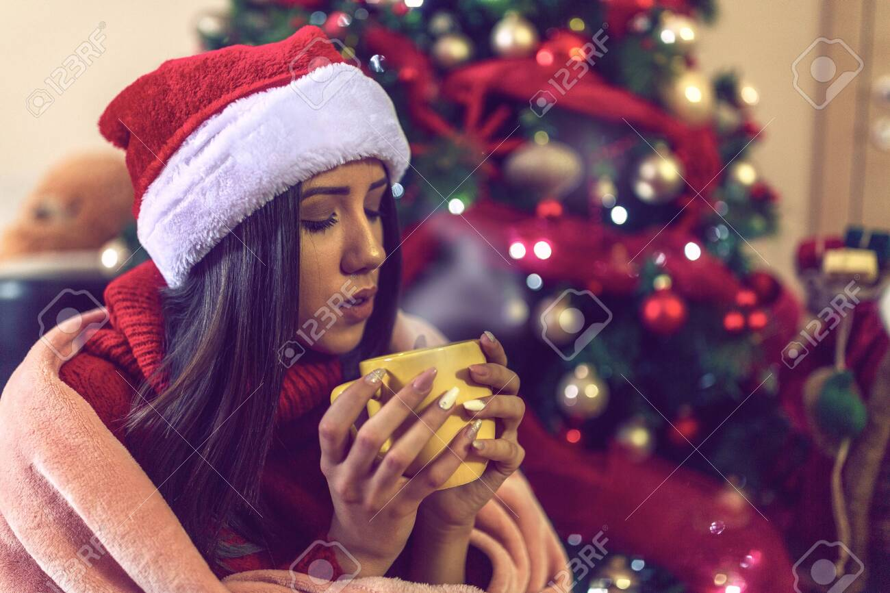 young girl in Santa hat drinking tea or coffee over christmas tree background at home - 133124277