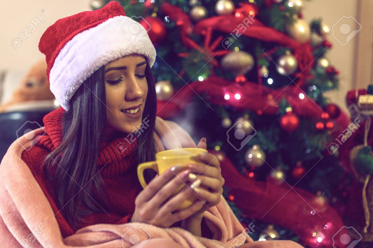 young woman in Santa hat drinking tea or coffee over christmas tree background at home - 133124282