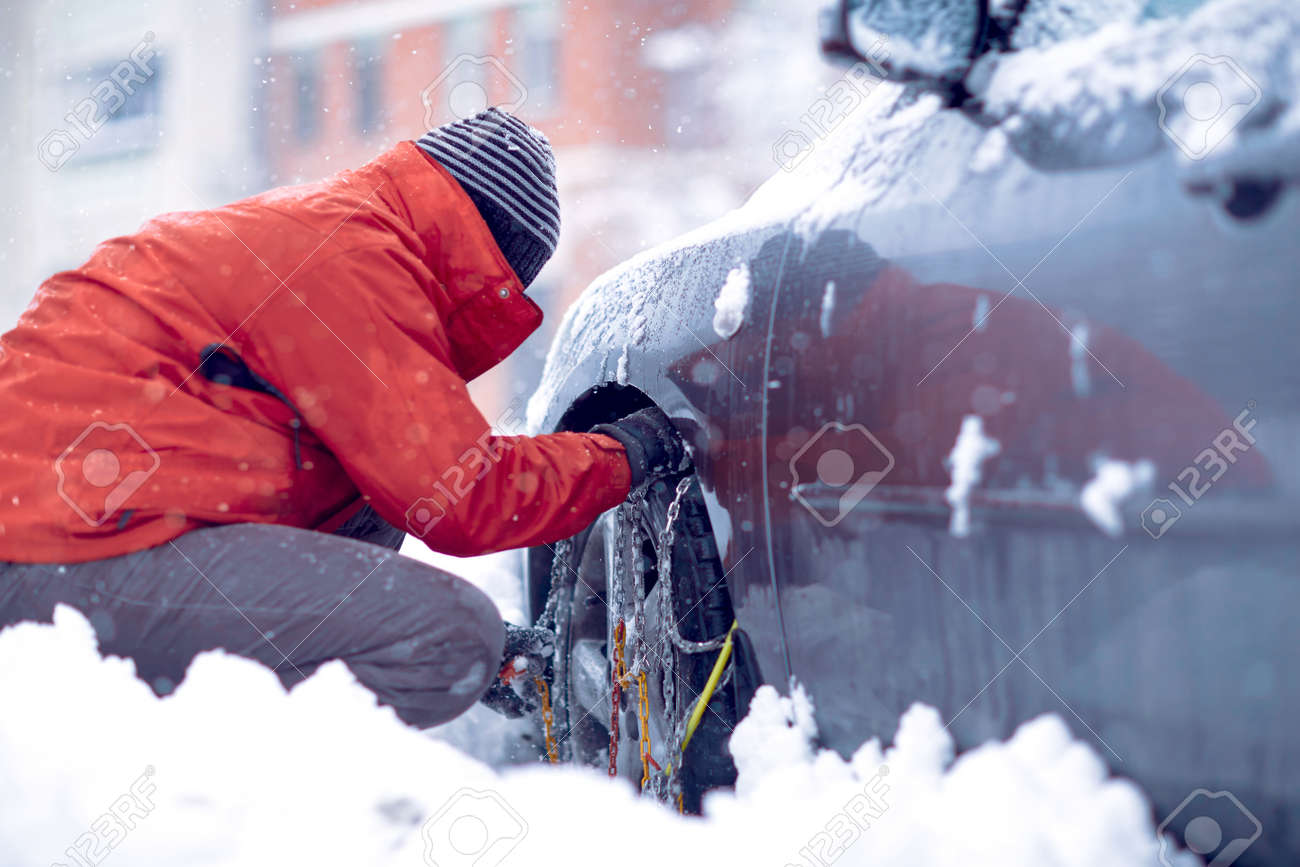Snow chains on the wheels of car.Man preparing car for travelling at winter snowy day. - 133124284