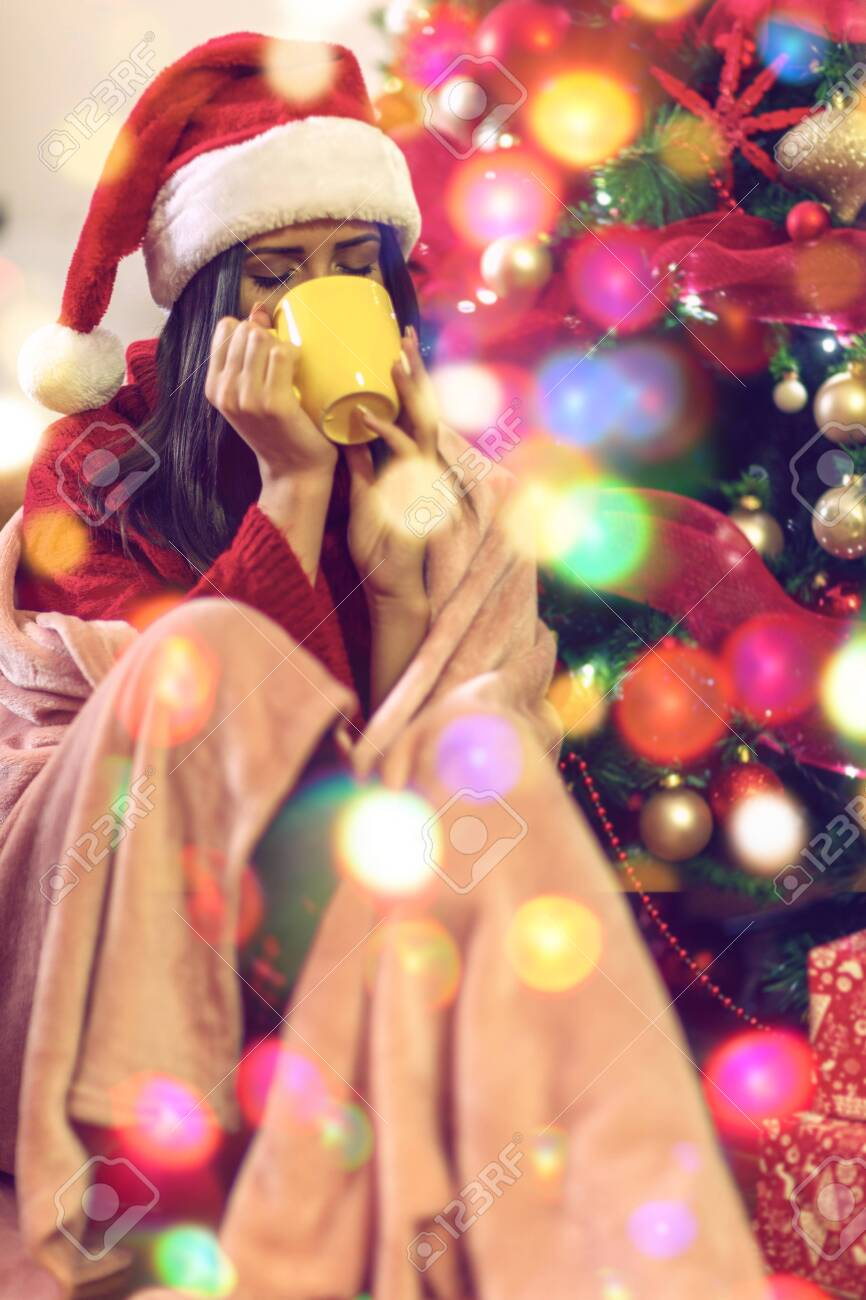Smiling woman sitting by the christmas tree and drinking hot tea - 134962251