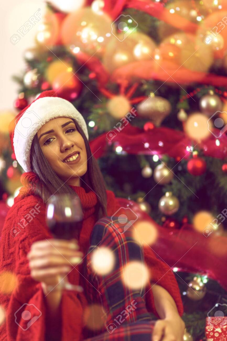 Woman toasting with red wine.holidays, winter and people concept - young smiling woman in Santa hat by Christmas tree at home. - 134962274