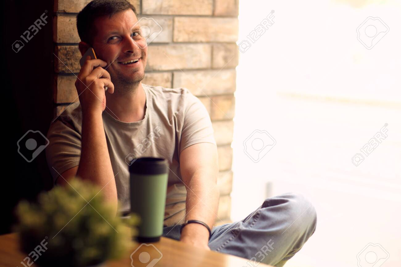 Smiling Young Man using smartphone in cafe.Man relaxing in cafe .Freelancer. - 134962642