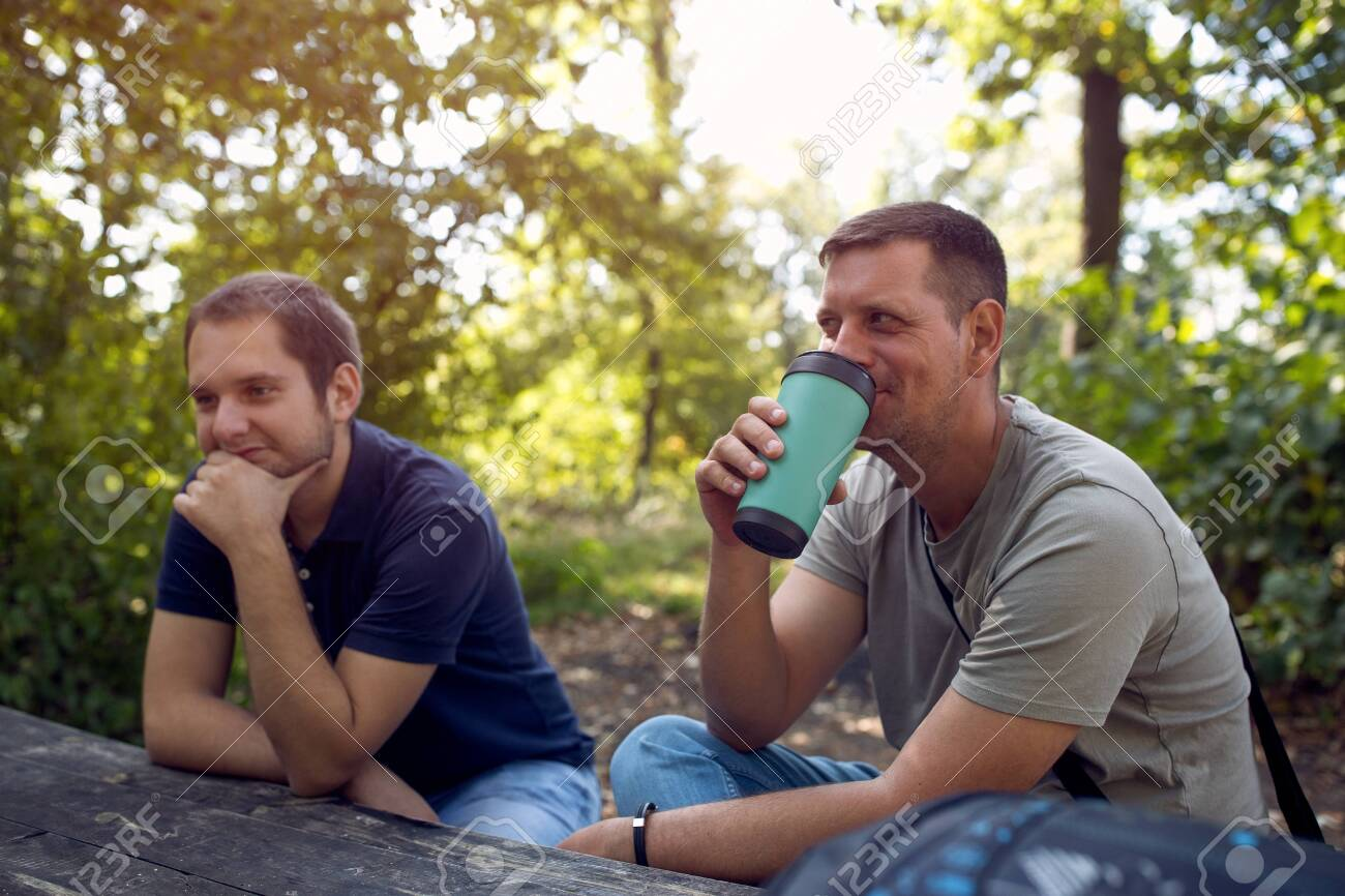 Young Men sitting in the park and enjoying peaceful sunny day and drink coffee - 134962646