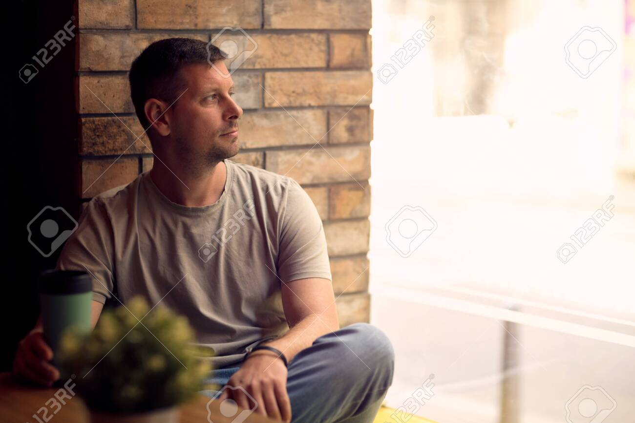 Young Man drinking coffee in cafe and looking away - 134962696