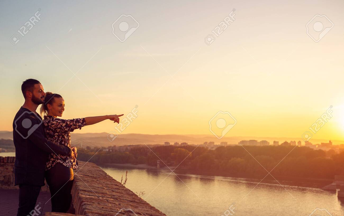 Smiling loving man and woman watching the sunset - 134962571