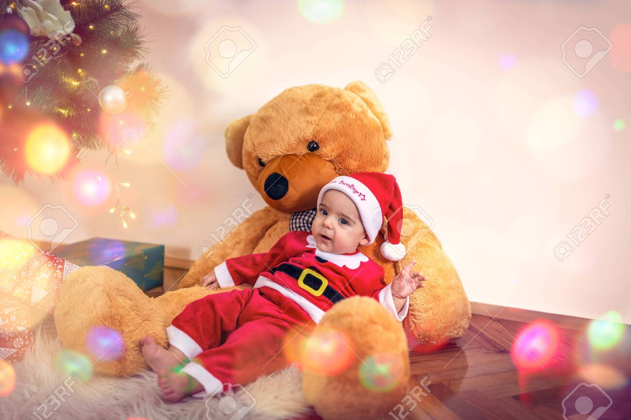 Little baby boy in Christmas Santa's costume with teddy bear on Christmas day.Happy baby boy wearing santa clothes. - 134962577