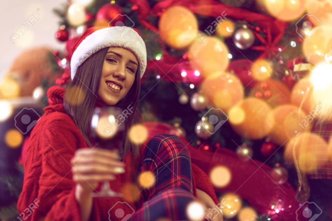 Smiling Woman with red wine, xmas tree.Happy young girl toasting with red wine - 134962406