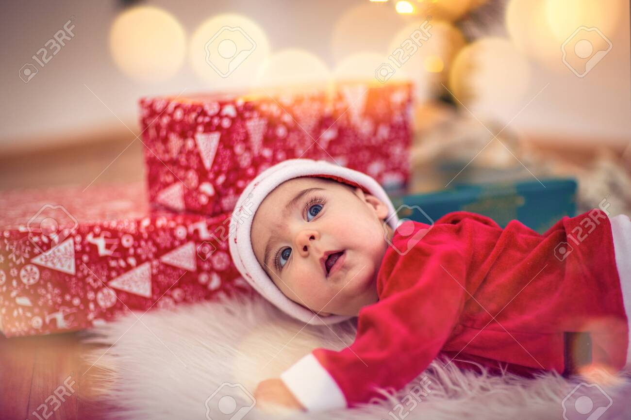 Cute smiling baby in Santa hat on floor at home. Christmas celebration - 134962445