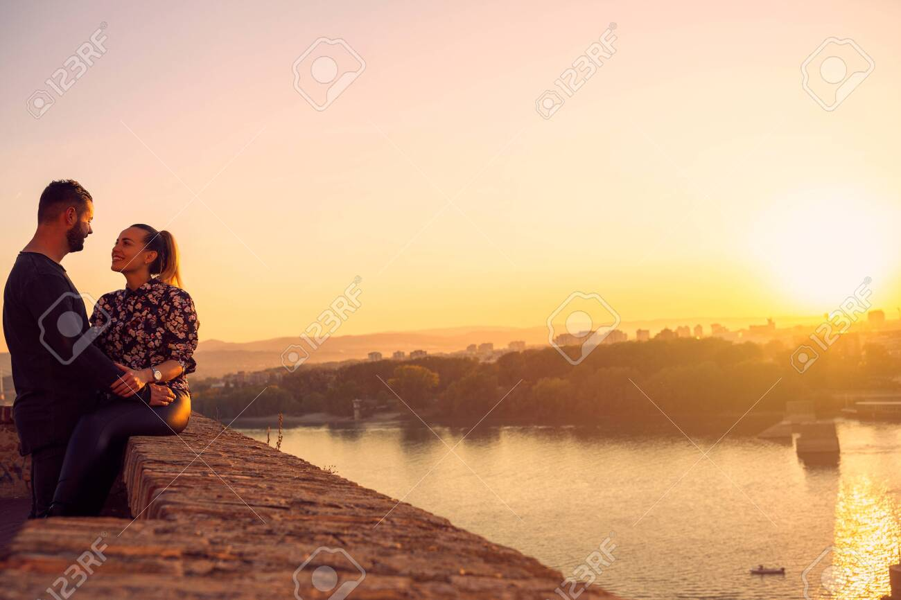 Smiling young man and woman spend time together at sunset - 134962456