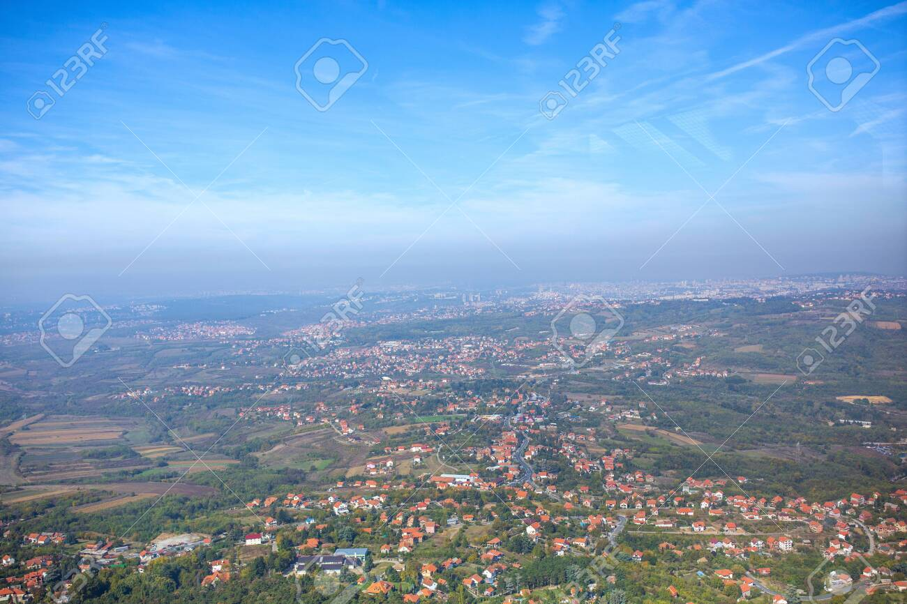 beautiful panorama of city downtown houses and church aerial view above the roofs with sun in summer - 134962467