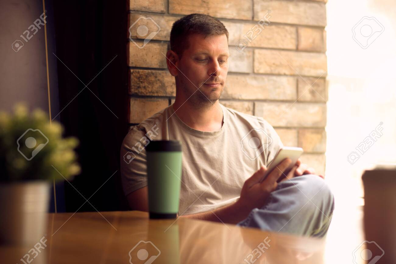 Young Man using smartphone in cafe.Man relaxing in cafe and drinking coffee. - 134962474