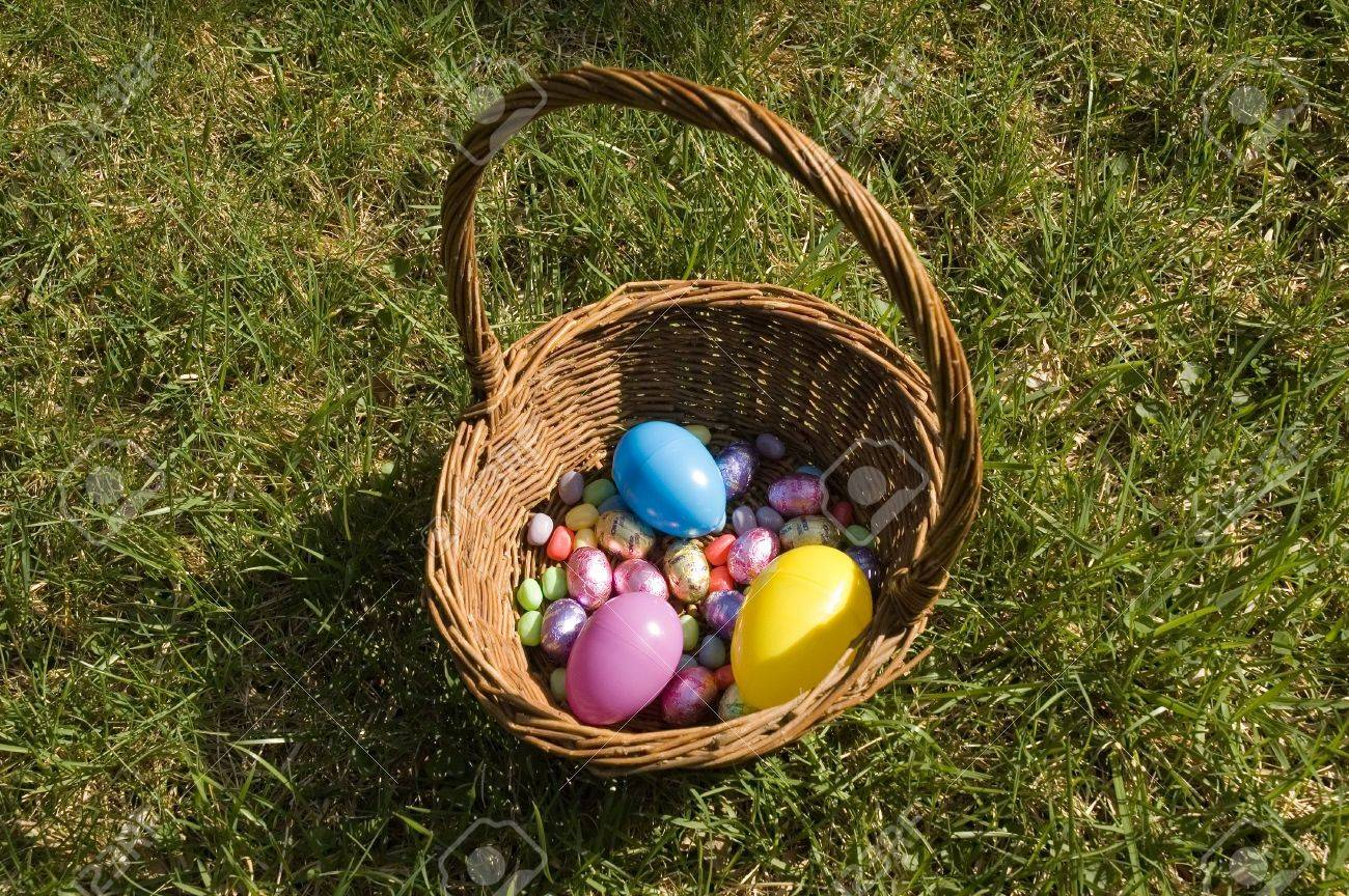 A Basket Filled With Plastic Easter Eggs And Egg Shaped Chocolate Candy On The Lawn Stock