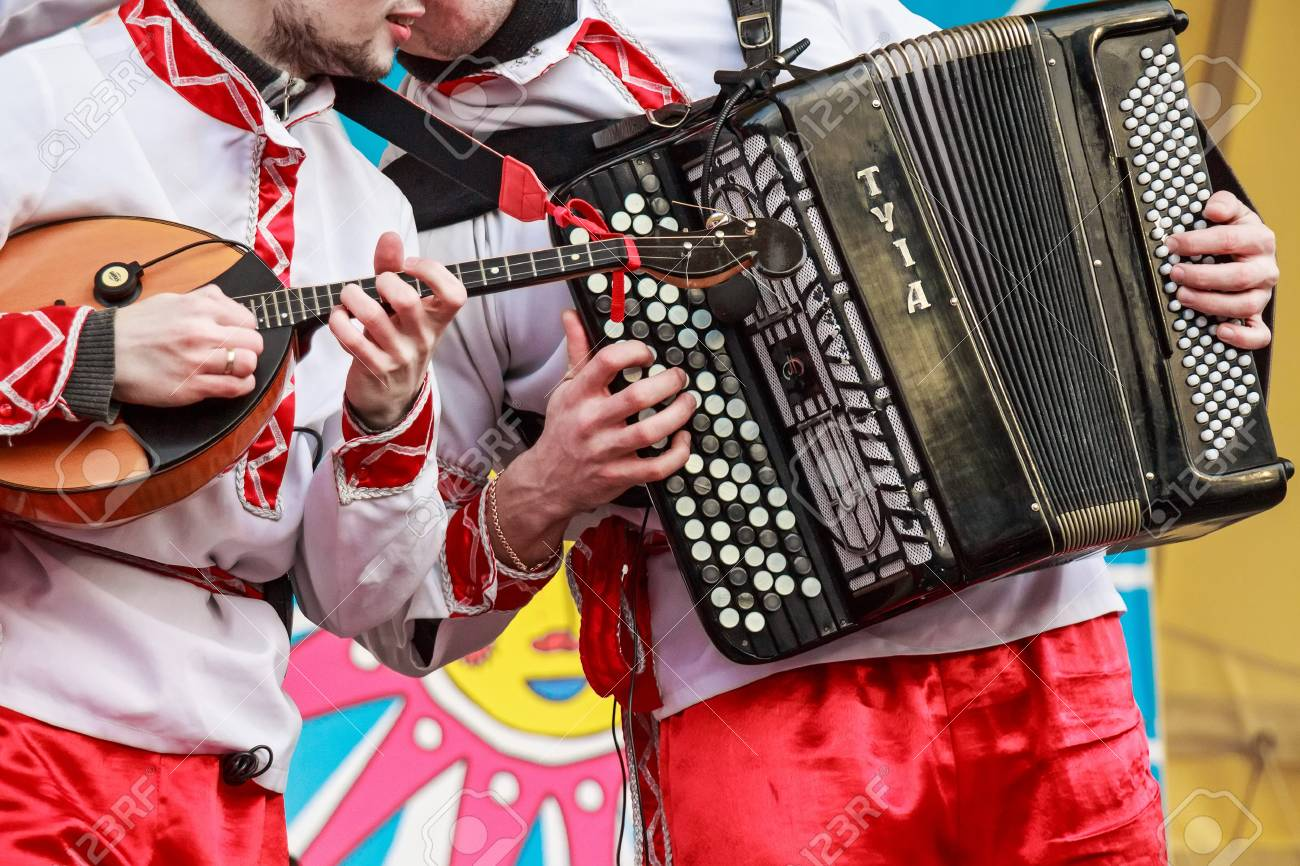 Close up musician playing domra and accordion on a Russian fair