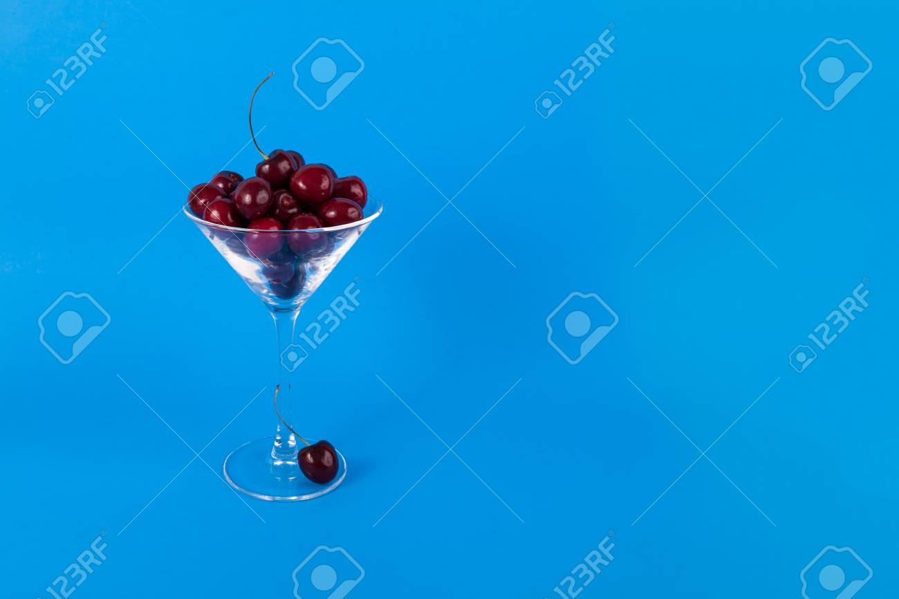 Dark red sweet cherries in martini class on a solid blue background